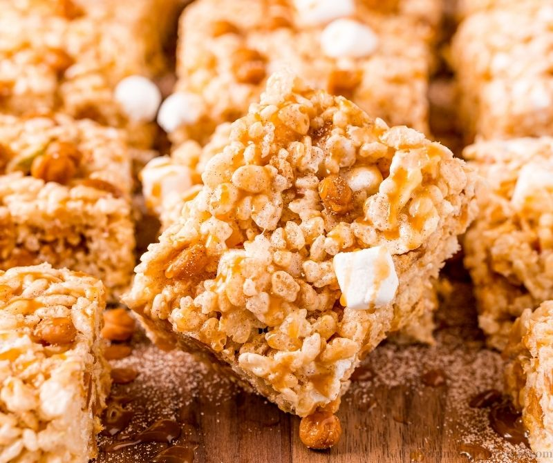 A tilted slice of the Apple Rice Krispies in front of more krispie's.