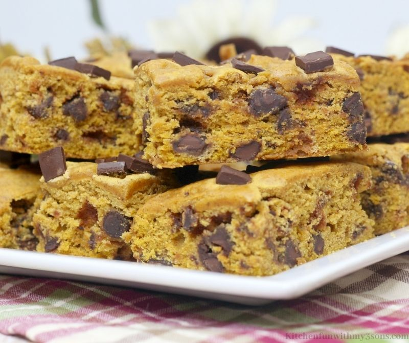 Multiple Chocolate Chunk Pumpkin Bars on a serving dish on a patterned cloth.