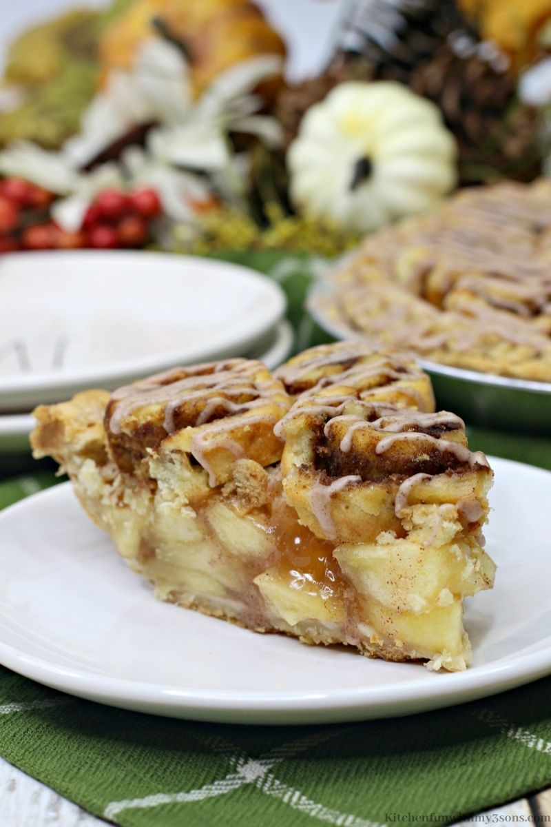 Cinnamon Roll Apple Pie Recipe with Fall decorations behind it and the whole pie as well.