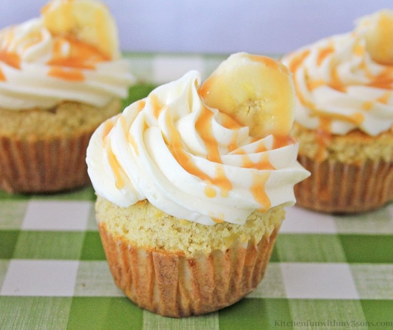 Close up of the Delicious Banana Caramel Cupcakes on a patterned green and white cloth.