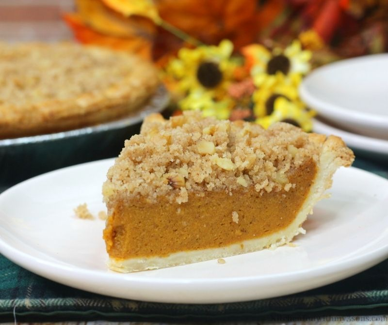 Delicious Pumpkin Streusel Pie with Fall decorations behind it.