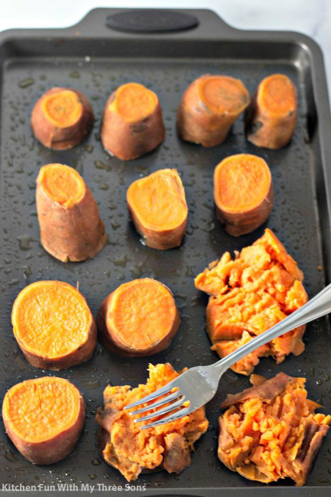 smashing sweet potatoes on a cookie sheet
