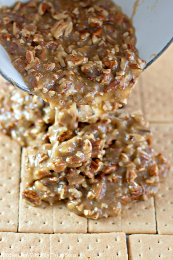 pouring hot pecan toffee over graham crackers