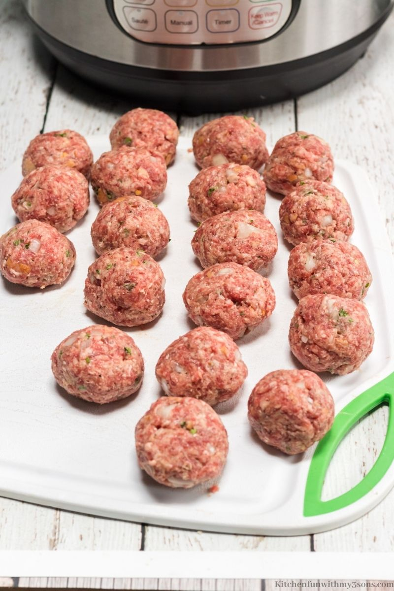 The meat rolled into balls on a cutting board.