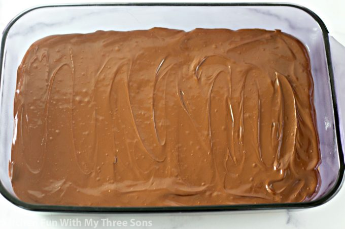 spreading melted chocolate over the peanut butter bars
