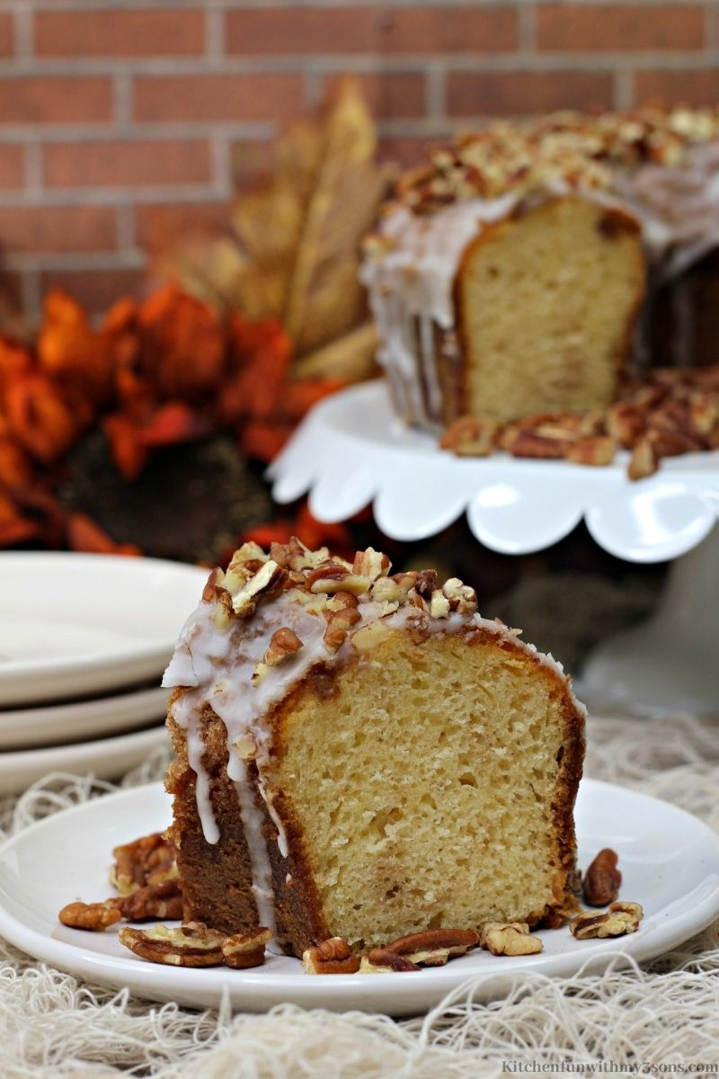 Pumpkin Bourbon Pecan Cake Recipe with fall decorations and the remaining cake behind it.