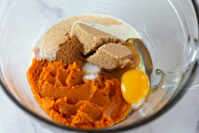 mixing together pumpkin, brown sugar, egg, cream, and spices in a clear batter bowl