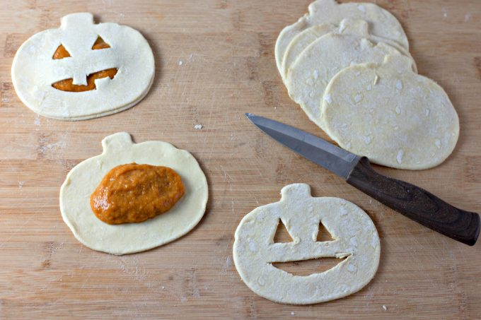 cutting jack-o-lantern shapes out of puff pastry