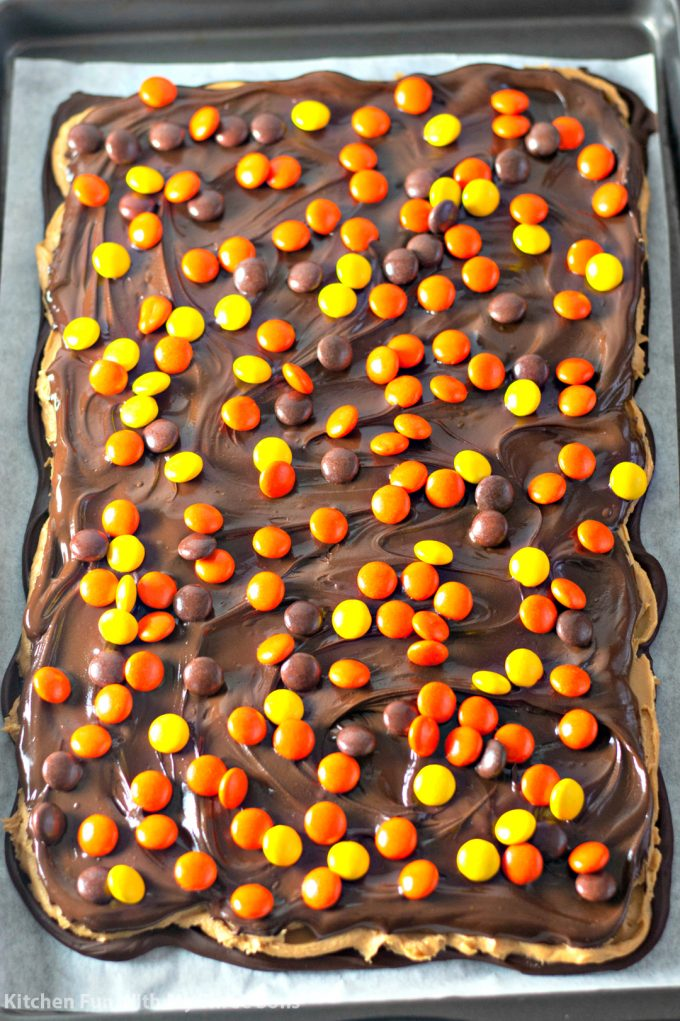 sprinkling Reese's Pieces over the candy bark