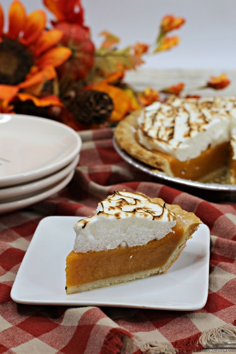 A slice of the Sweet Potato Pie Recipe with Marshmallow Meringue on a patterned cloth.
