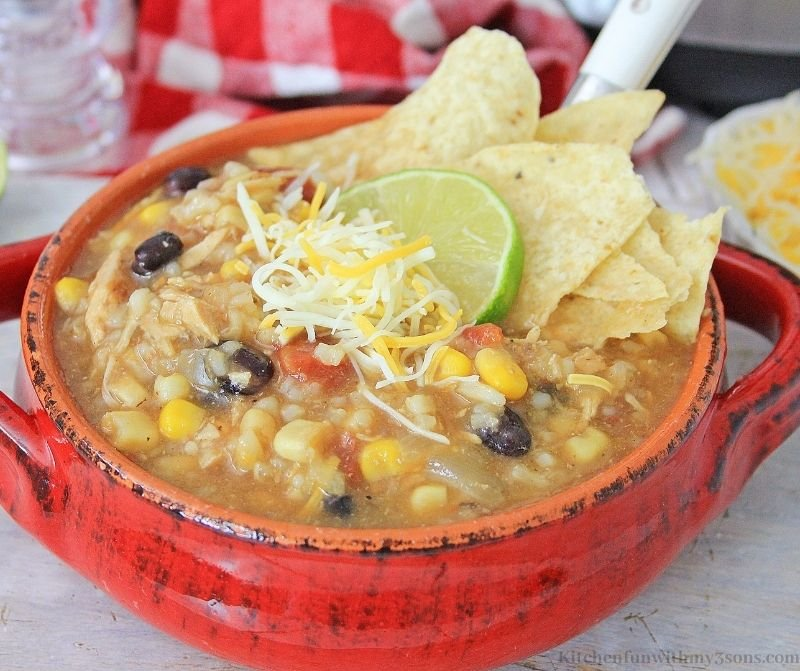 Tex Mex Instant Pot Chicken and Rice Soup topped with lime and cheese.