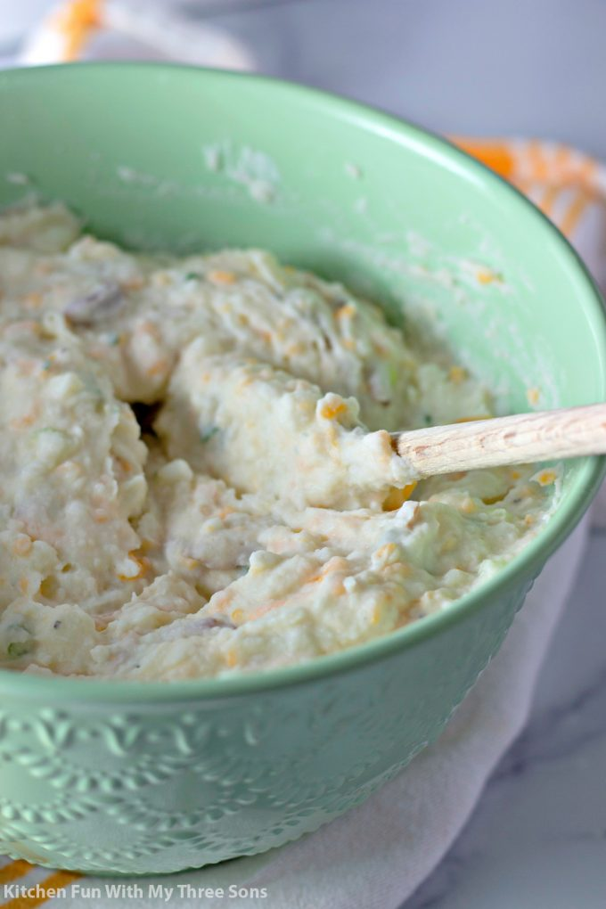 mashed potatoes in a bowl with a wooden spoon
