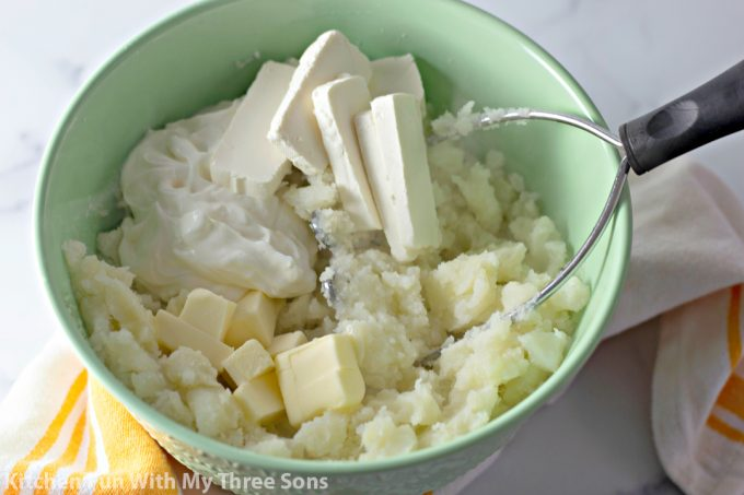 mashing potatoes in a mint green bowl with cream cheese, butter, and sour cream