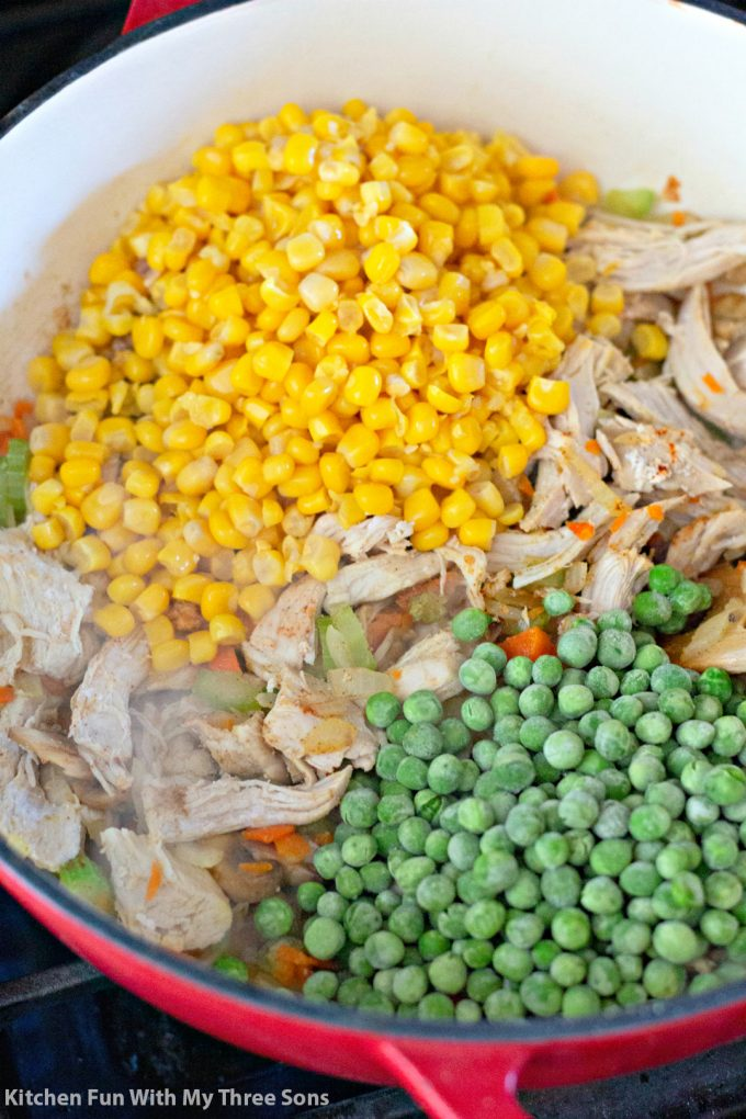 adding shredded chicken, corn, and peas to the pot