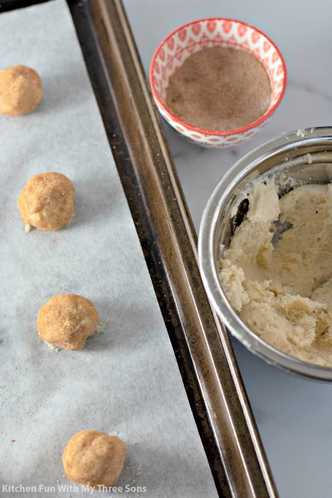 rolling cookie dough balls in cinnamon and sugar