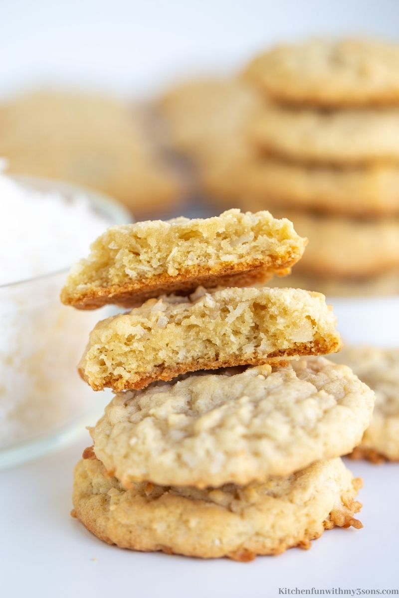Easy Coconut Cookies stacked on top of each other with one cookie split in half.