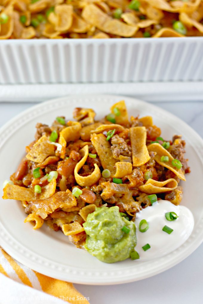 Easy Fritos Pie Recipe on a white plate with sour cream and guacamole