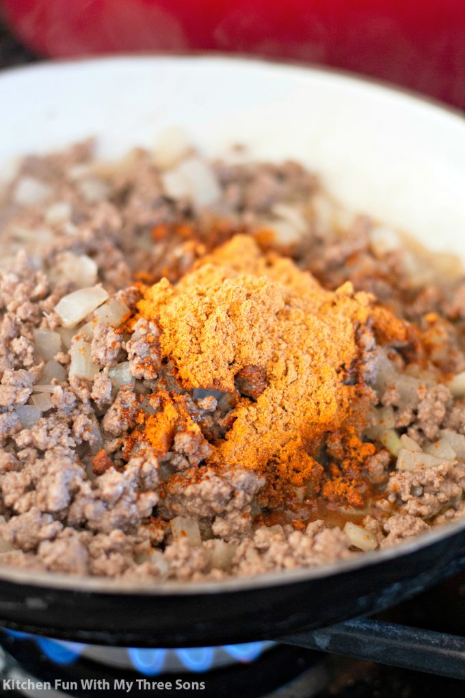 cooked ground beef in a pan with onions and taco seasoning