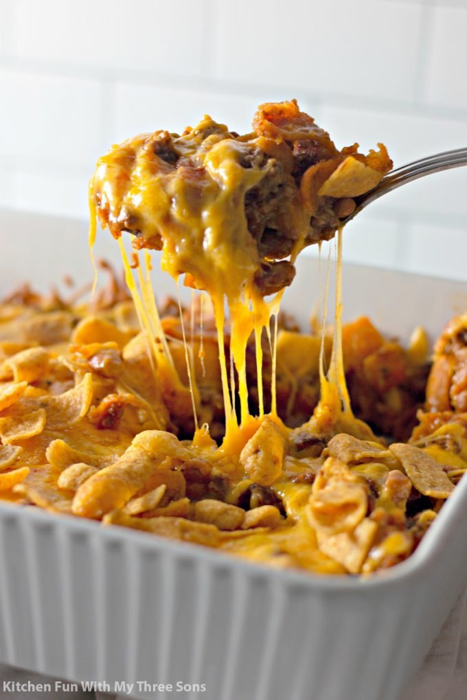 spooning a serving of Easy Fritos Pie Recipe