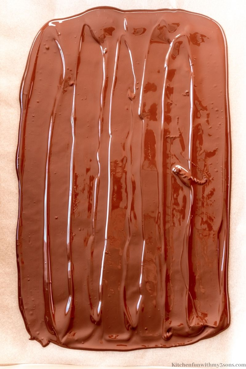 The melted chocolate spread onto the prepared sheet.