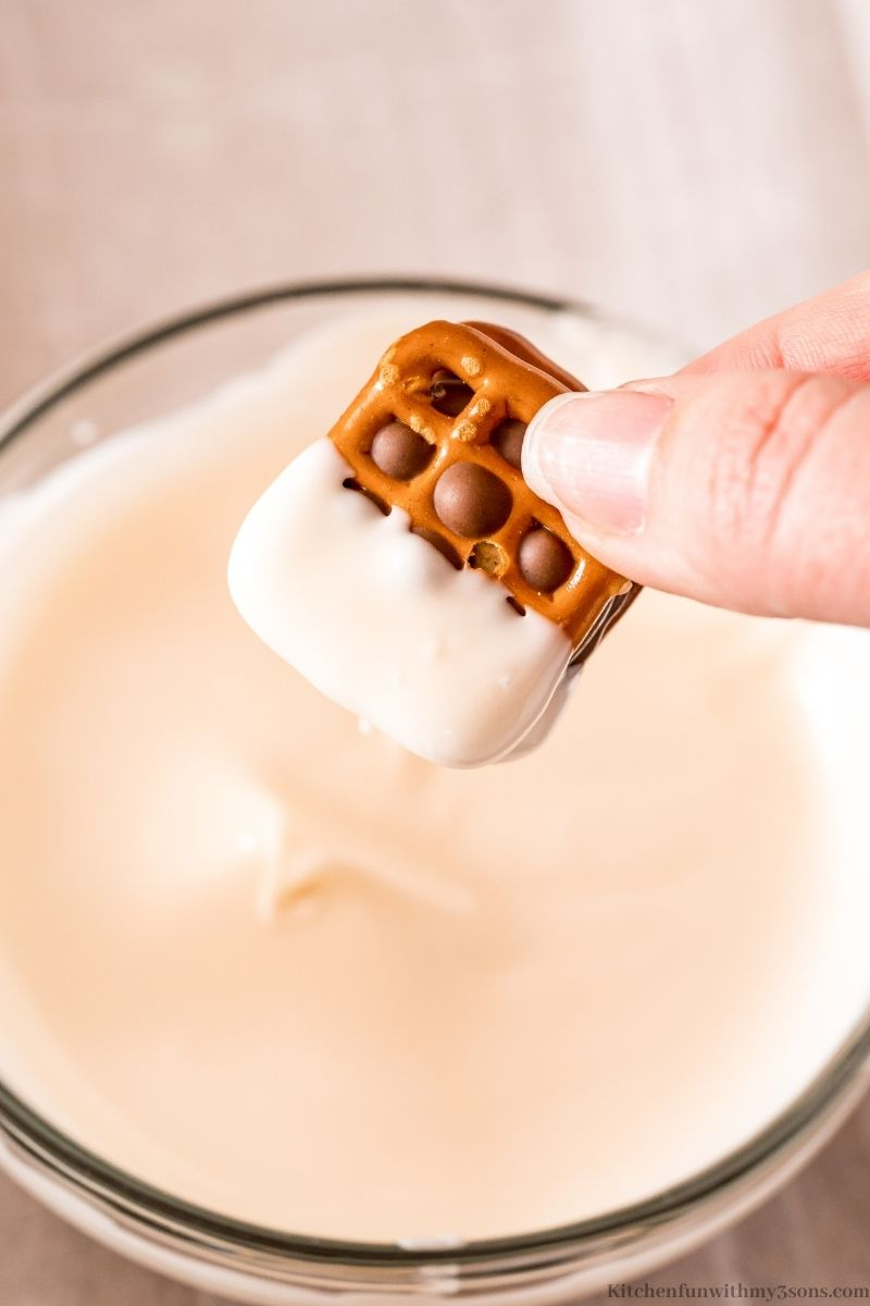 Dipping the pretzels into the melted white chocolate.