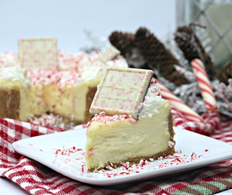 Ghirardelli Peppermint Cheesecake Recipe with candy canes and pine decorations behind it.