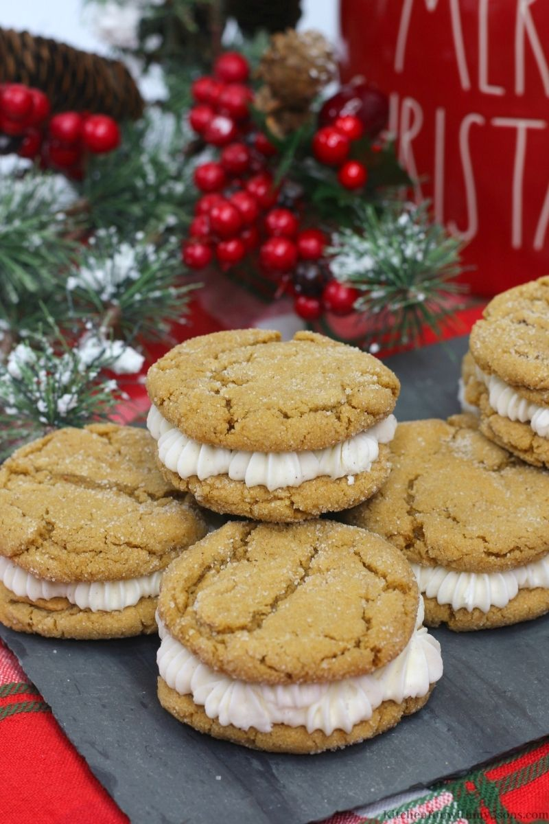 Gingerbread Sandwich Cookies with snow frosted branches behind it.