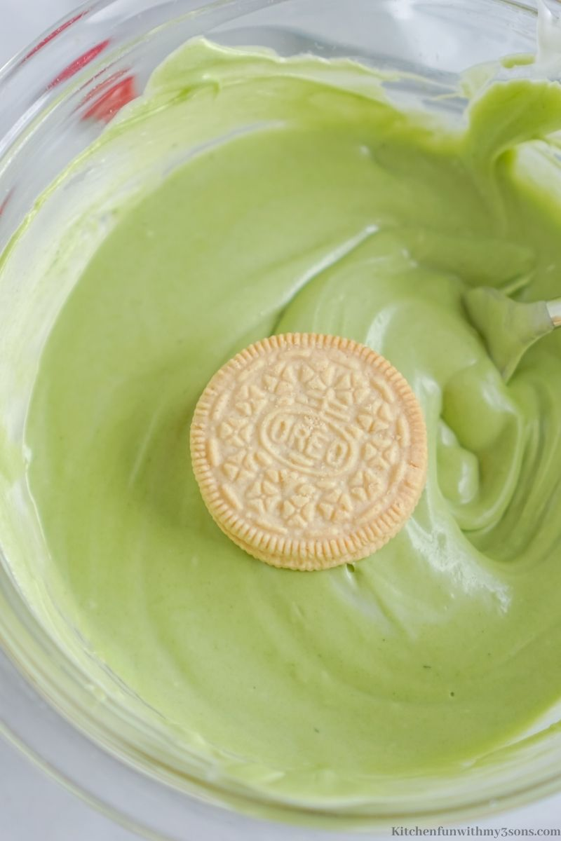 Coating the Oreos into the green batter.