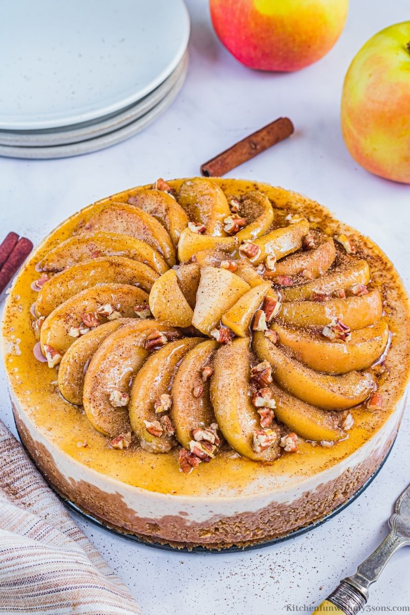 The whole Instant Pot Apple Cinnamon Cheesecake topped with apples and walnuts.