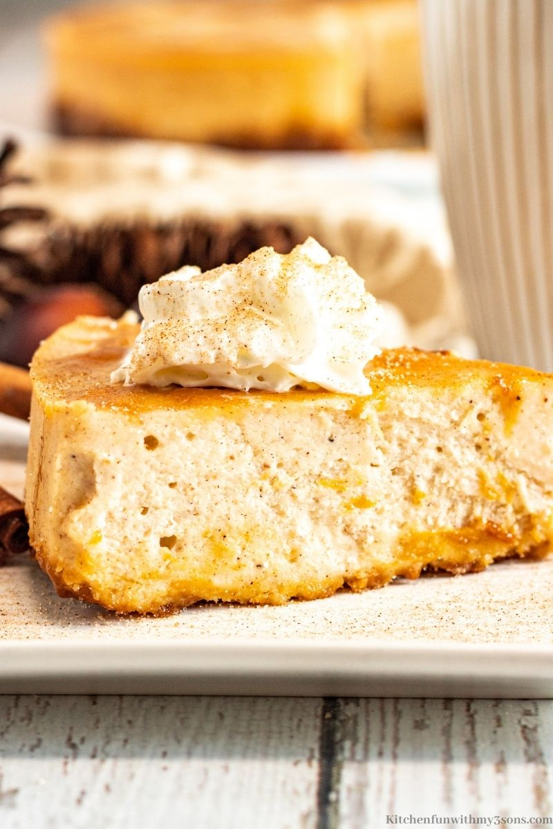 Instant Pot Eggnog Cheesecake Recipe with cinnamon sticks on the plate.