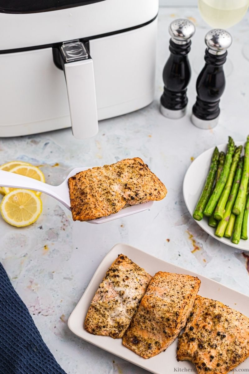 Lemon Pepper Air Fryer Salmon being lifted up with a spatula.