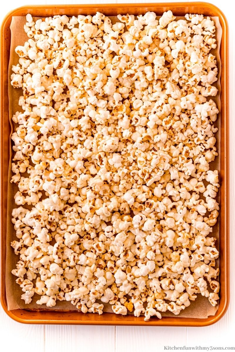 Popcorn spread out on a prepared sheet.