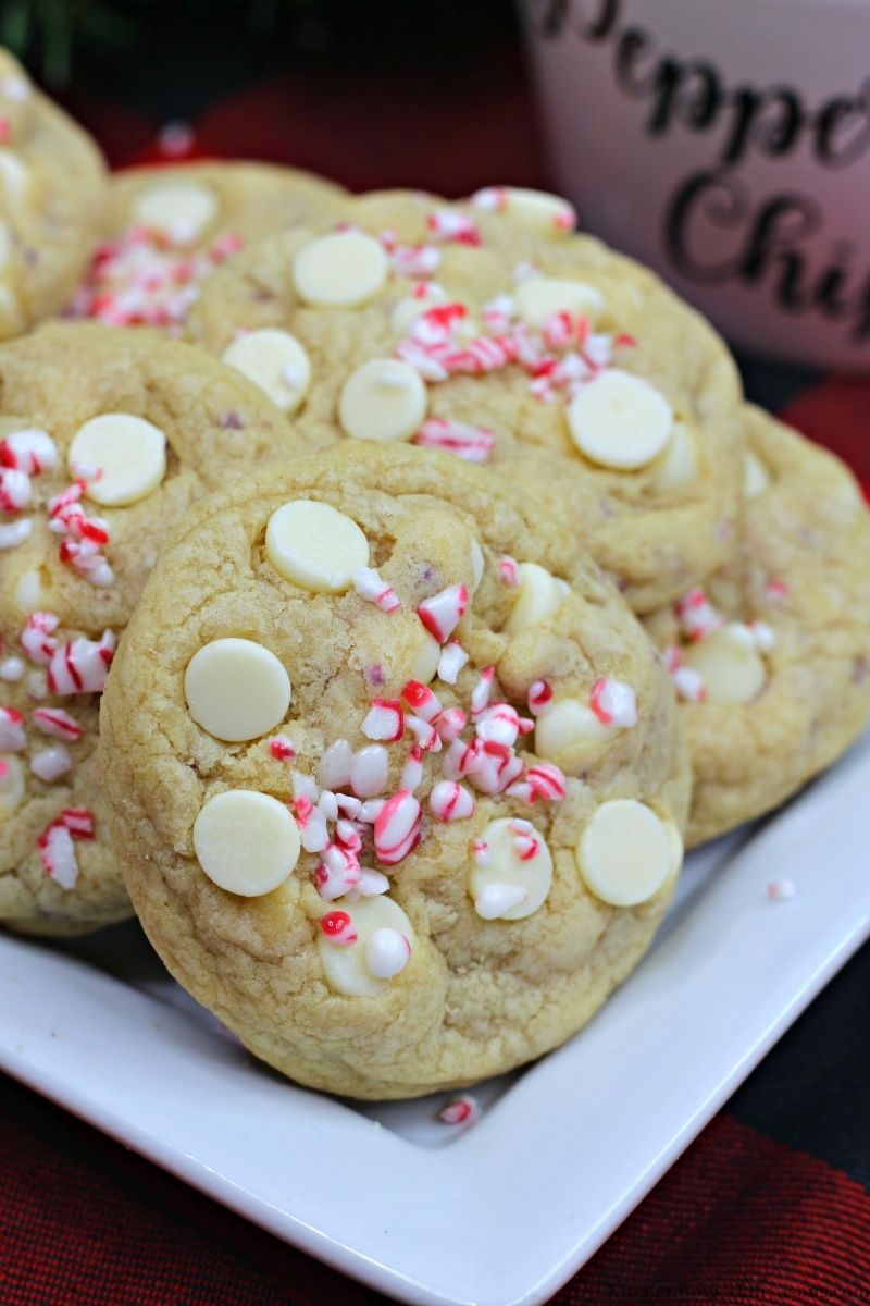 Peppermint White Chocolate Chip Cookies with a cup next to is filled with peppermint.