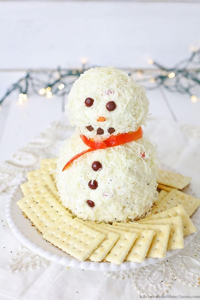 Snowman Christmas Cheese Ball Recipe with Christmas lights behind it.