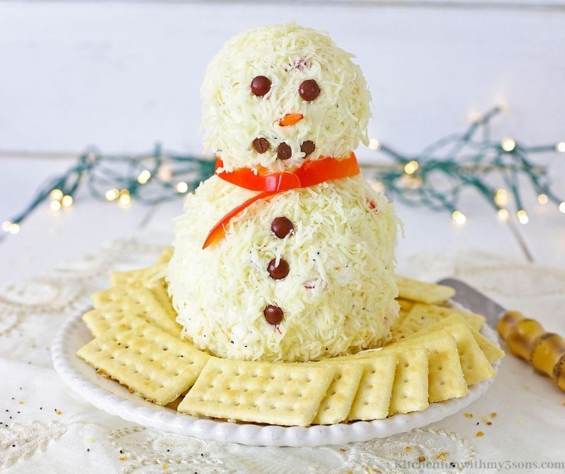 Snowman Christmas Cheese Ball surrounded by crackers.