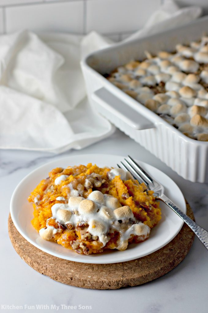 Sweet Potato Casserole with Pecan Streusel and Marshmallows on a white plate with a fork