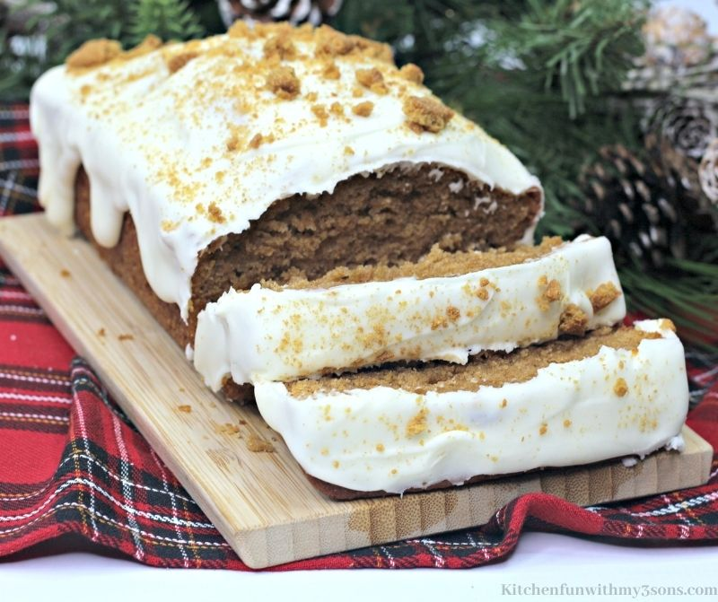 The Best Gingerbread Loaf Recipe with branches and pine cone decorations behind it.