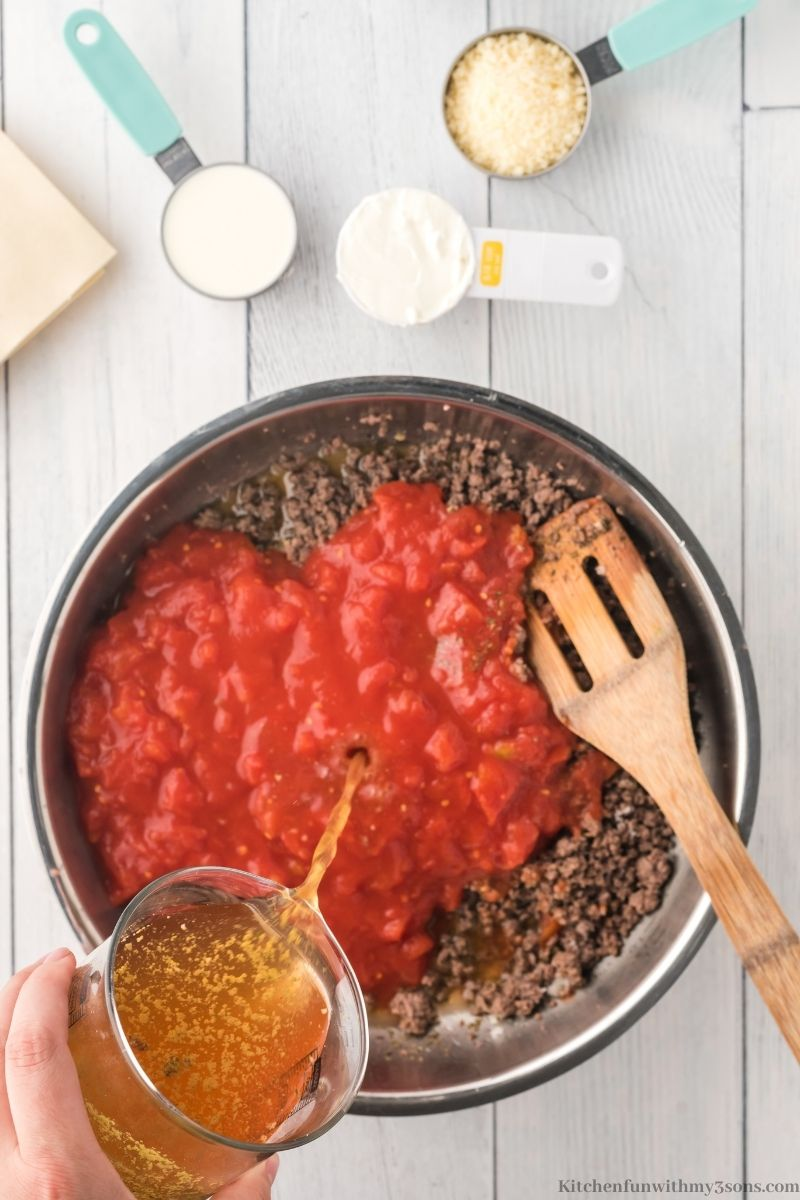 Adding the ground beef and tomatoes together in the saucepan.