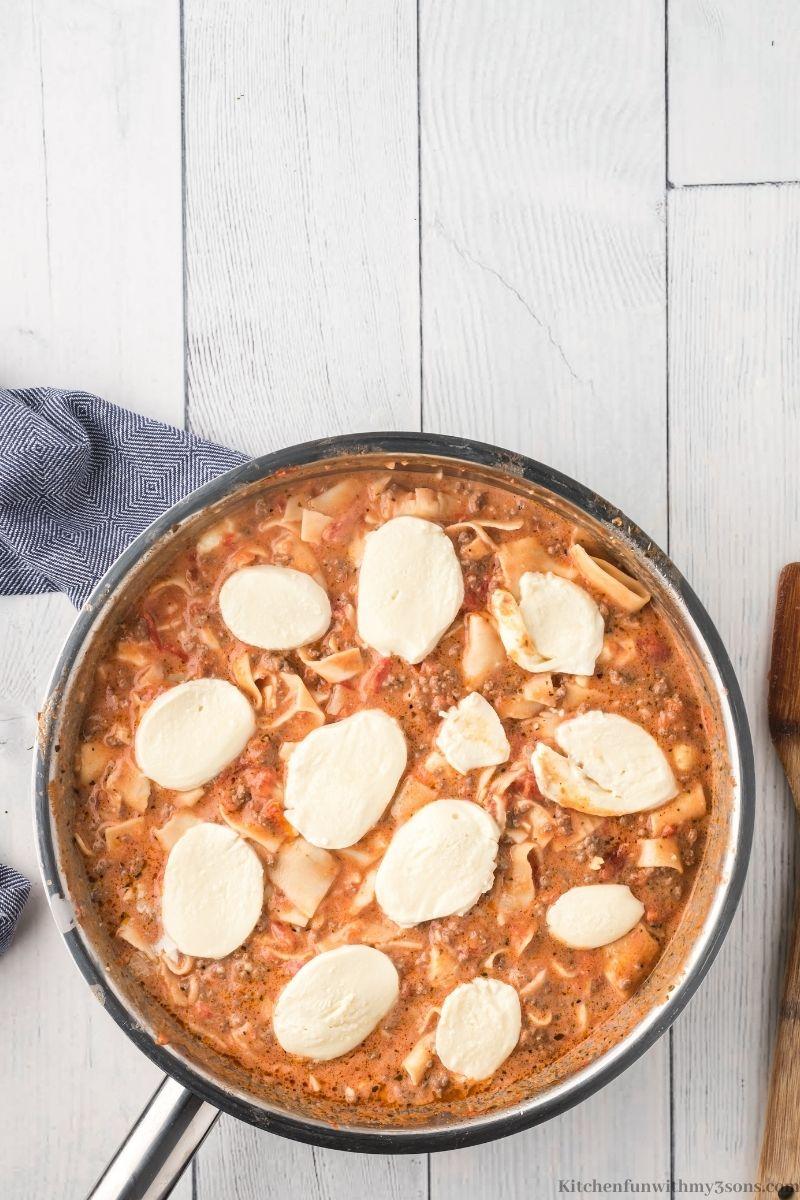 Adding slices of Mozzarella on top to melt.