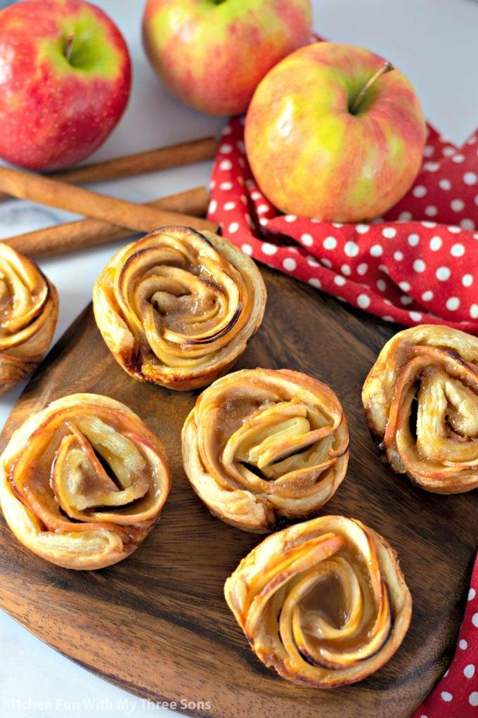 a wooden platter filled with Caramel Apple Rose Tarts