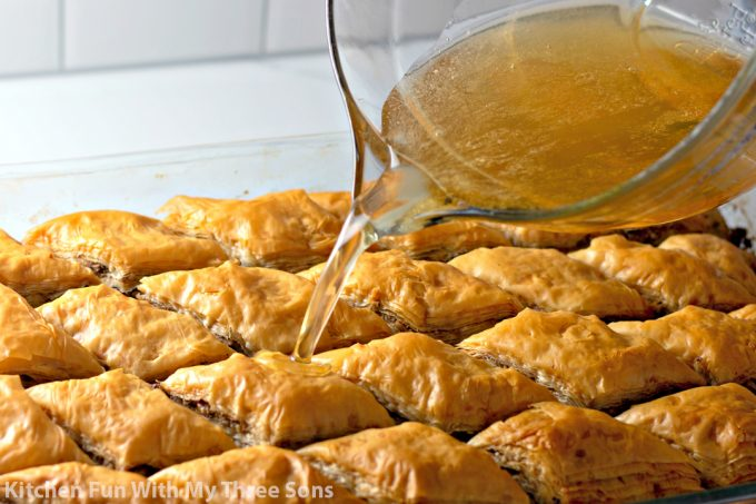 pouring honey syrup over freshly baked baklava