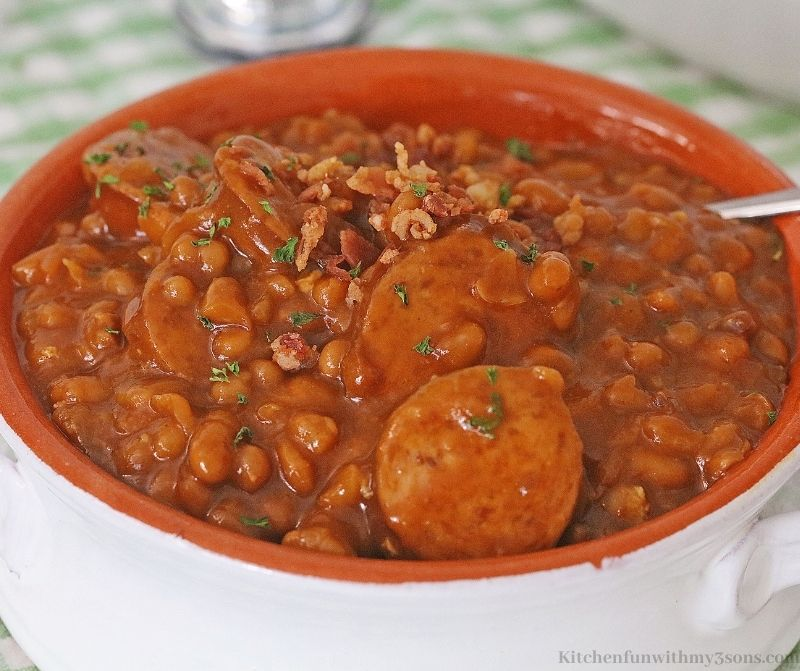 Crock-Pot Kielbasa Sausage and Beans Recipe topped with bacon.