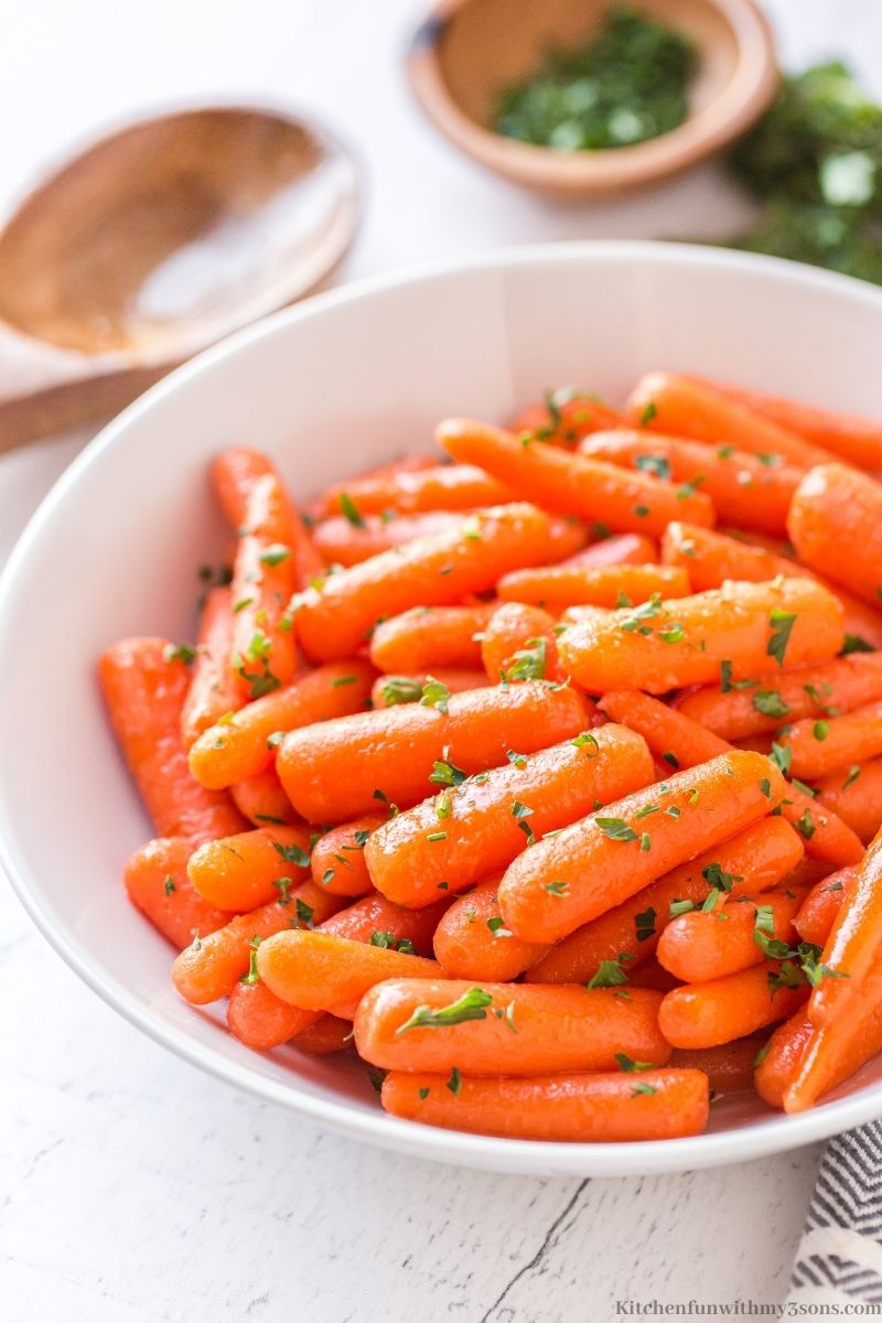 Easy Honey Glazed Carrots with a wooden spoon.