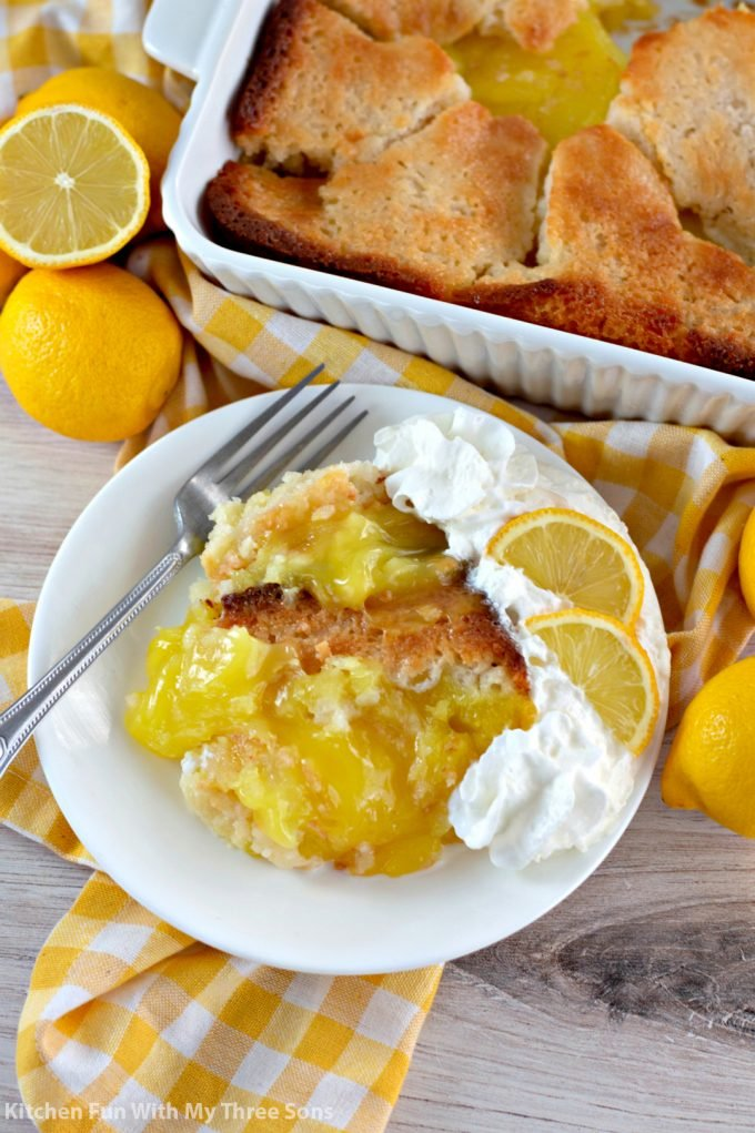 Magic Lemon Buttermilk Cobbler on a white plate with lemons and whipped cream