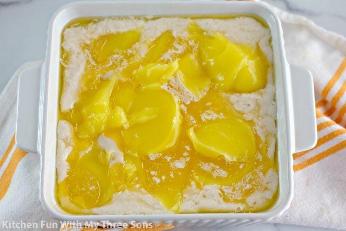 scooping lemon pie filling over the batter