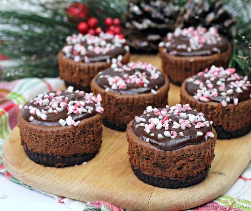 Five of the Mini Chocolate Peppermint Cheesecakes on a wooden board.