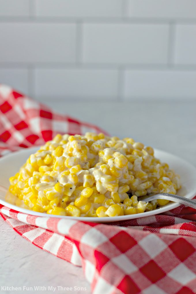Crock Pot Creamed Corn Recipe on a plate with a red and white checkered napkin