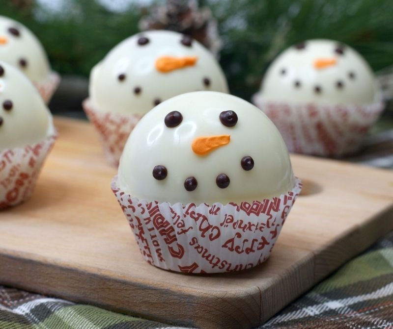 Snowman Hot Cocoa Bombs on a wooden board.
