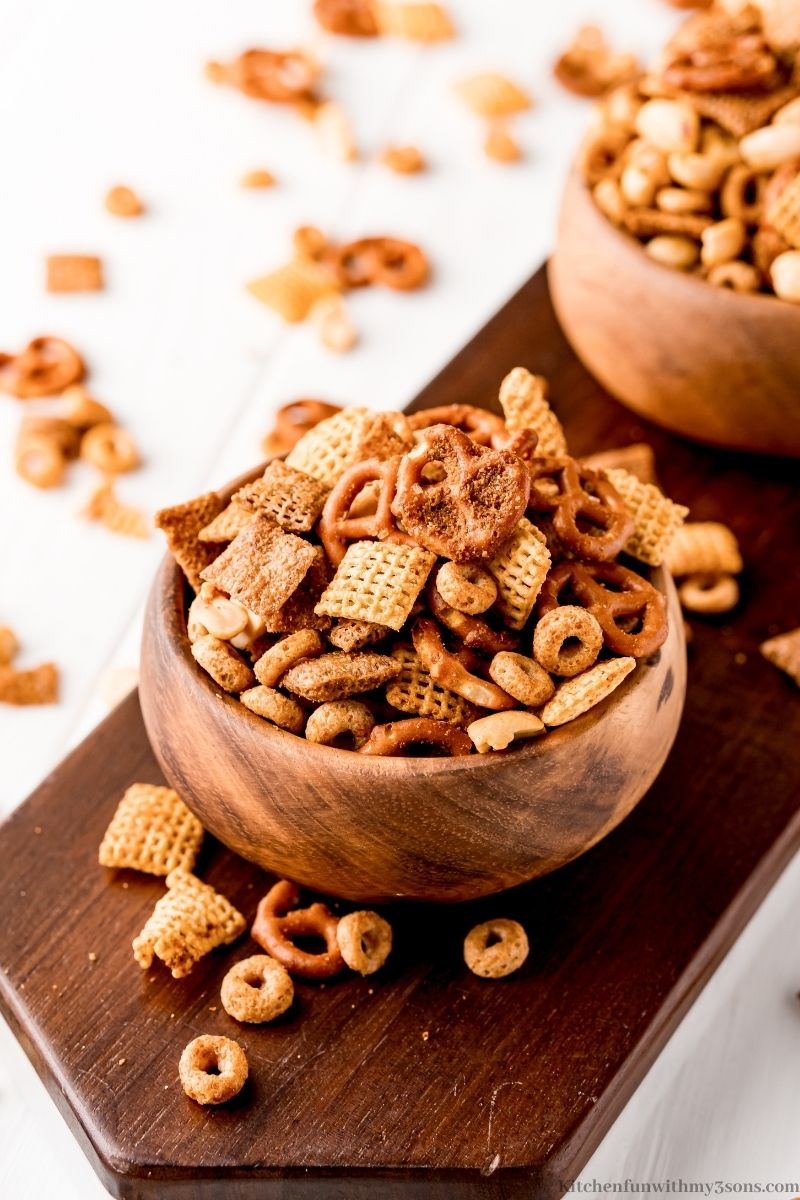 Texas Trash Snack Mix on a wooden paddle.