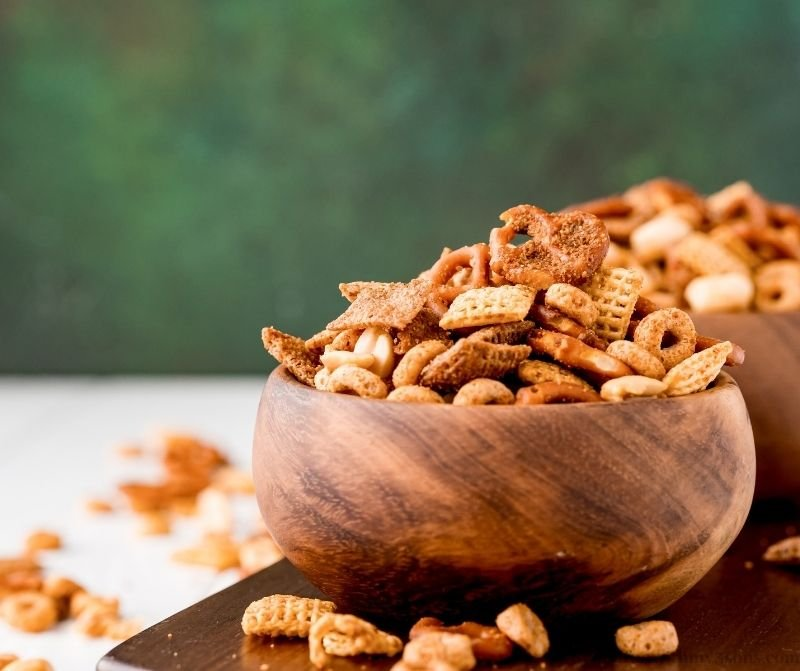 Texas Trash Snack Mix in bowls with a green background.